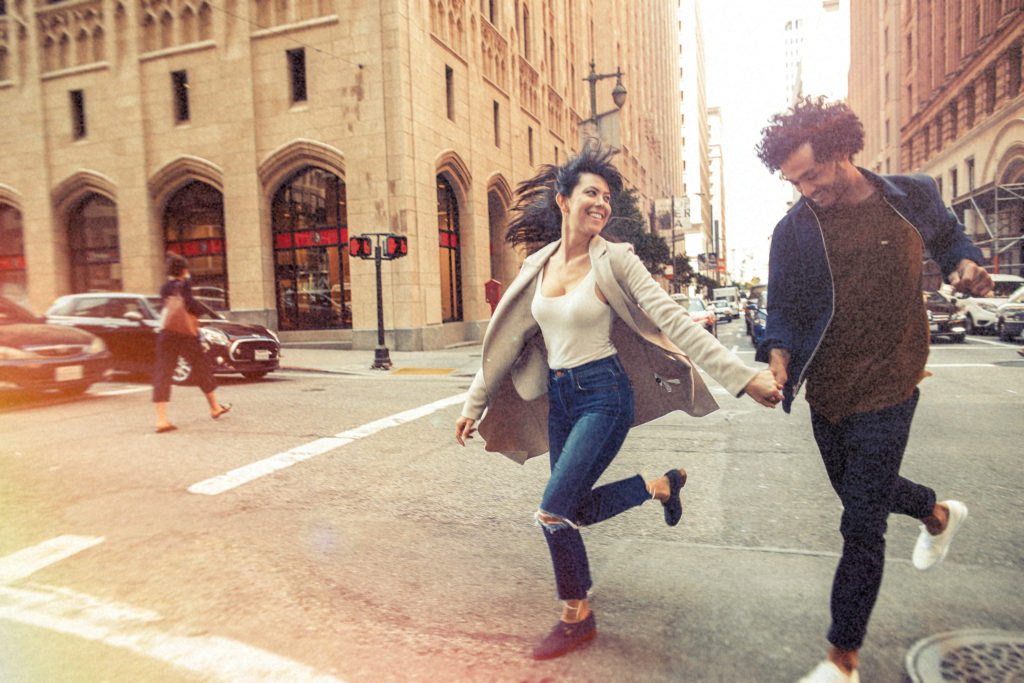 joyous young couple running across city streets